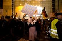 PEGIDA member waving at loud counter demonstrators.