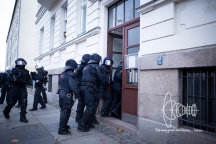 Riot police forces break window of house door to attack antifa activists standing behind a fence.