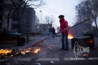 A resident lady tries to extinguish a lit barricade with a street sign.