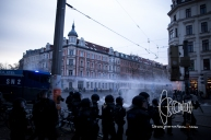 A water cannon fires into a local store on the street corner.
