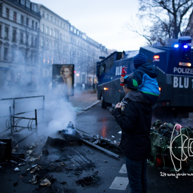 A man with his son on his shoulders watches a water cannon extinguish barricades. The boy has a miniature fire extinguisher.