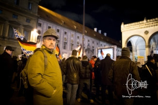A man poses in classical, german military outfit in front of Feldherrnhalle in Munich.