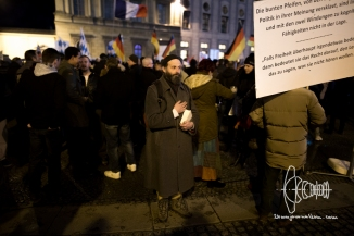 As the german national anthem is played a PEGIDA activist holds his hand on his heart.
