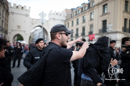 Neonazi hooligan throwing a couner-protestor at policemen.