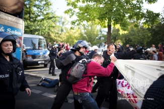 Policeman punches demonstrators.