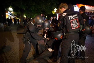 Riot police officer pulls person up at the throat.