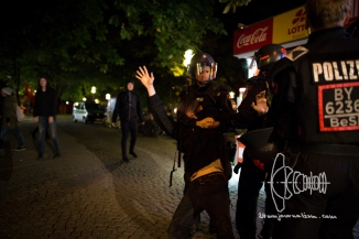 Riot police officer pulls person off the site at the head.