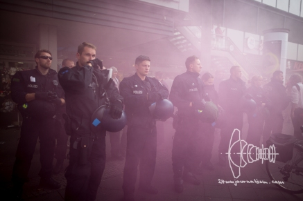 Policemen standing in smoke of lit pyrotechnics.