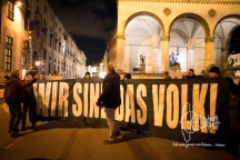 Neonazis arrive with sparkles and banner, mocking victims of November pogroms and pose in front of historically charged Feldherrnhalle.