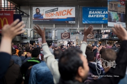 Munich citizens and refugees cheer as the hard journey finds an end.