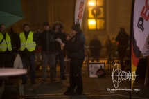 Karl Heinz Statzberger holds talk in front of PEGIDA Munich, wearing jacket with 'National. Revolutionary. Socialist' imprinted on the back.