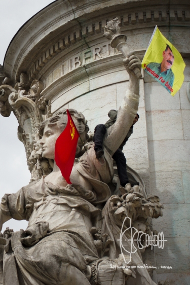 "A protestor clims on a statue and attaches a ""Freedom for Öcalan"" flag below the words ""Liberty"""