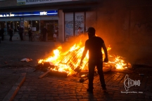 Man standing in front of burning barrier.